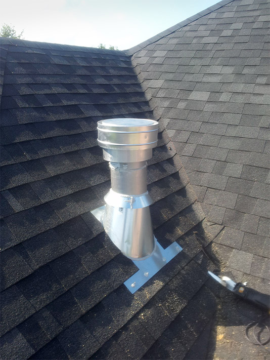 The homeowner chose to have the vent pipe exposed for this installation.  Note the purpose-built flashing and lapping of the shingles over the flashing to create a watertight barrier.